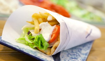 Il pitagyros: carne di maiale arrostita nel pane pita farcita con pomodoro, cipolla, patate fritte, insalata, salsa tzatziki