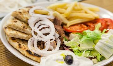 Il pitagyros al piatto: carne di maiale arrostita farcita con pomodoro, cipolla, patate fritte, insalata, salsa tzatziki, pita